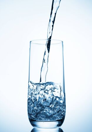 Foto per water pouring into glass on blue background - Immagine Royalty Free