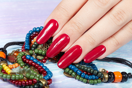 Photo pour Hand with long artificial manicured nails colored with red nail polish - image libre de droit