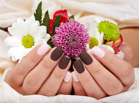 Photo pour Hands with pink and purple manicured nails holding a bouquet of flowers - image libre de droit