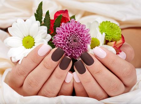 Foto de Hands with pink and purple manicured nails holding a bouquet of flowers - Imagen libre de derechos
