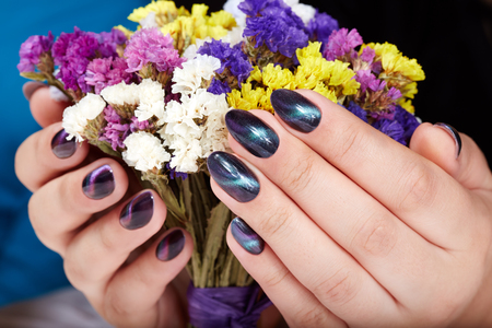 Photo pour Hands with manicured nails with cat eye design holding a bouquet of flowers - image libre de droit