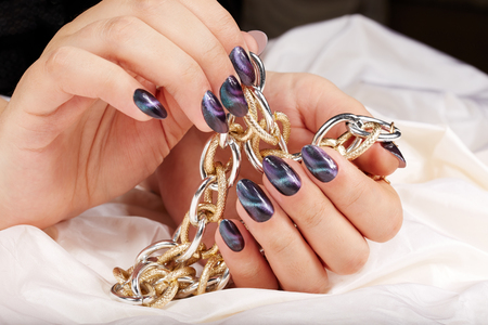Photo pour Hands with manicured nails with cat eye design holding a necklace - image libre de droit