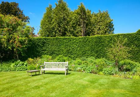 Foto de Wooden bench in a summer garden - Imagen libre de derechos