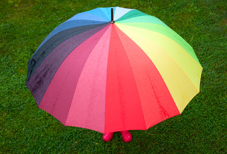 Little girl wearing red rubber boots hiding behind colorful umbrella in the rain