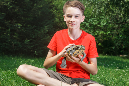 Photo for Cute teenager boy wearing red t-shirt sitting on a lawn in a summer garden holding turtle looking at camera smiling - Royalty Free Image