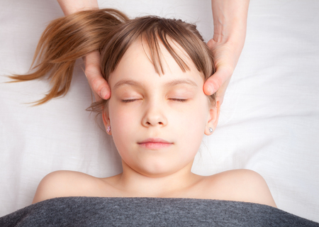 Photo pour Elementary age girl's head being manipulated by an osteopath - an alternative medicine treatment - image libre de droit