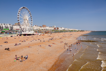 Foto de BRIGHTON, UK - JUN 5, 2013:View along the  Brighton Beachfront with the Ferris Wheel promenade and vacationer on shingle beach pictured from the Brighton Palace Pier on a sunny summer day - Imagen libre de derechos