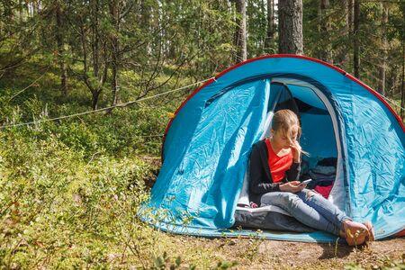 Foto de Tween girl sitting alone in camping tent focused on her smartphone messaging or checking social media during summer holidays - Imagen libre de derechos