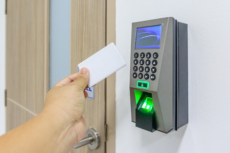 Foto de electronic key- card and finger scan access control system to lock and unlock doors , Hand Holding Keycard To Open Door - Imagen libre de derechos