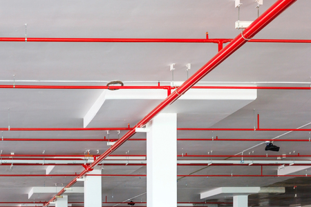 Foto de Fire sprinkler system with red pipes is placed to hanging from the ceiling inside of an unfinished new building. - Imagen libre de derechos