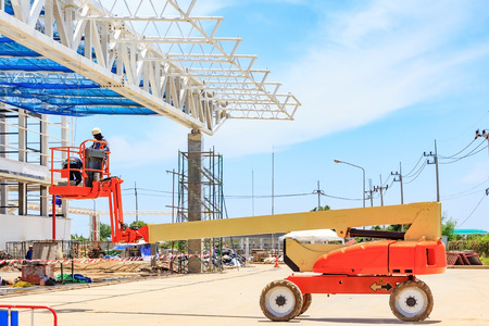 Foto de Worker man on a Scissor hydraulic Lift table Platform towards a factory roof at a construction site - Imagen libre de derechos