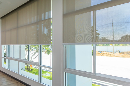 Photo pour Roll Blinds on the windows, the sun does not penetrate the house. Window in the Interior Roller Blinds. Beautiful Blinds on the Window, the Sun and Heat Protection, the Perfect Windows Interior Decor - image libre de droit