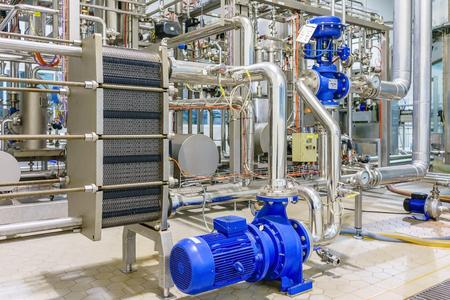 Foto de metalic plate in heat exchange machine and pump in the food industrial plant - Imagen libre de derechos