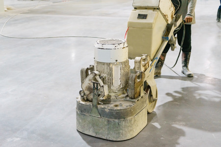 Foto de Women worker using polishing machine for smoothing surface to finish concrete slab.concrete floors - Imagen libre de derechos