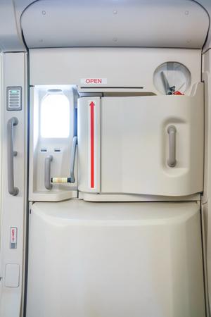 Foto de Closeup shot of Emergency exit on an aircraft, view from inside of the plane. - Imagen libre de derechos