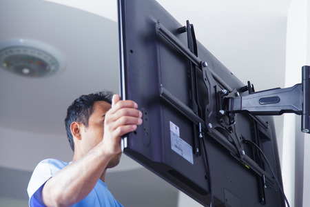 Photo pour Installing mount TV on the wall at home or office - image libre de droit