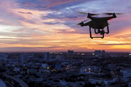 Foto de Silhouette of drone flying above city at sunset - Imagen libre de derechos