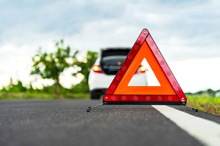 Photo pour Problems car and a red triangle warning sign on the road - image libre de droit