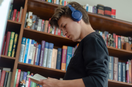 Photo for The teenage listens to music and reads book in front of library at home - Royalty Free Image