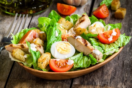 Photo pour Caesar salad with croutons, quail eggs, cherry tomatoes and grilled chicken in wooden plate on dark rustic table - image libre de droit