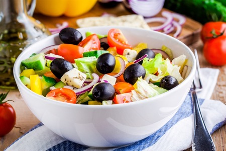 Photo pour Greek salad of organic vegetables with tomatoes, cucumber, red onion, olives and feta cheese - image libre de droit