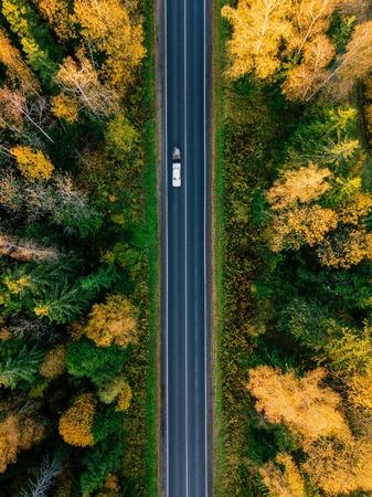 Photo pour Road in the colored autumn forest aerial view - image libre de droit