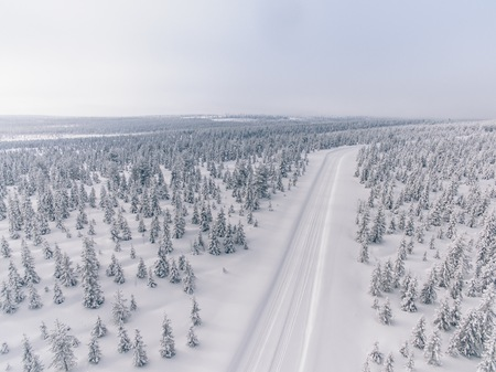 Photo pour Aerial view of the road in the winter snow forest in Finland, Lapland - image libre de droit