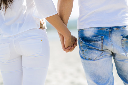 Foto de Romantic couple holding hands on a beach - Imagen libre de derechos