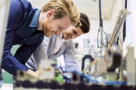 Foto de Two young handsome engineers working on electronics components and fixing broken chips - Imagen libre de derechos