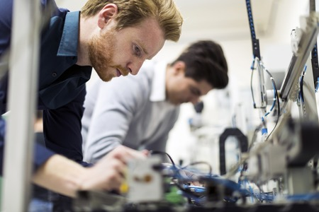 Photo for Two young handsome engineers working on electronics components and fixing broken chips - Royalty Free Image