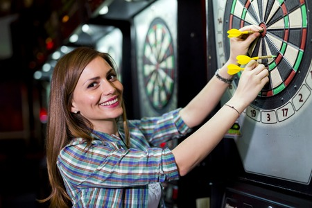 Photo for Young beautiful woman playing darts in a club and smiling - Royalty Free Image