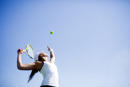Photo pour Beautiful female tennis player serving outdoor - image libre de droit