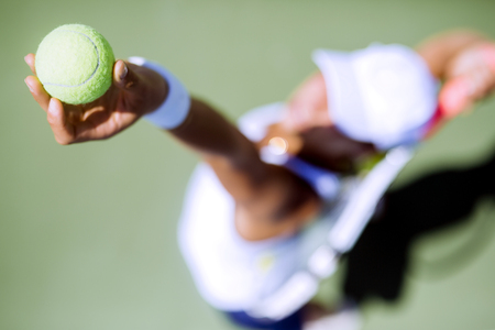 Beautiful female tennis player serving outdoor and a closeup of the serve from above