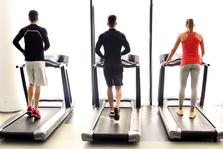Foto per Group of young people using treadmills in a fitness center - Immagine Royalty Free