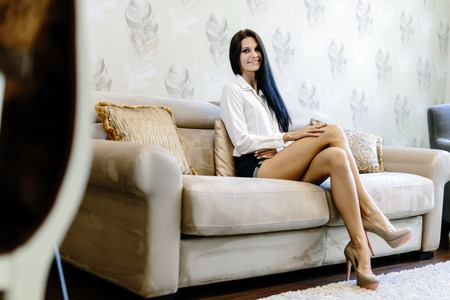Foto de Elegant and woman sitting on a sofa in a luxurious room and smiling - Imagen libre de derechos