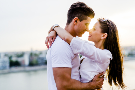 Photo pour Young romantic couple hugging and about to kiss in beautiful sunset - image libre de droit