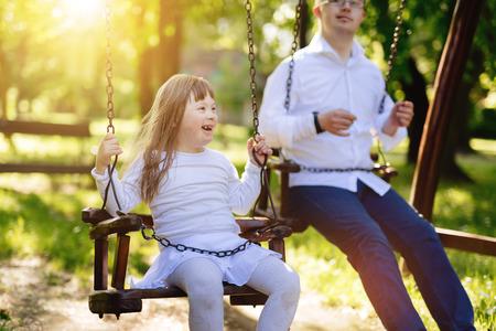 Foto de Happy child with down syndrome enjoying swing on playground - Imagen libre de derechos