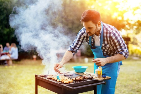 Photo for HAndsome male preparing barbecue outdoors for friends - Royalty Free Image