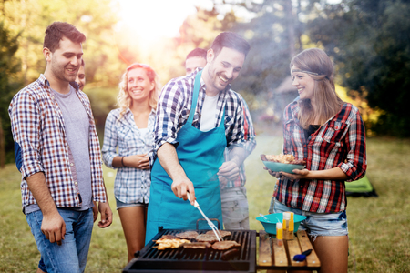 Photo for Friends camping and having a barbecue in nature - Royalty Free Image