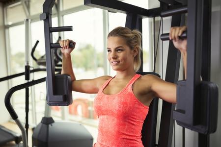 Foto de Beautiful woman doing chest exercises in gym - Imagen libre de derechos