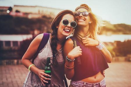 Photo pour Happy friends laughing and having fun outdoors at concert - image libre de droit