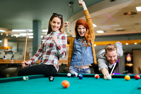 Photo for Happy friends enjoying playing pool together - Royalty Free Image