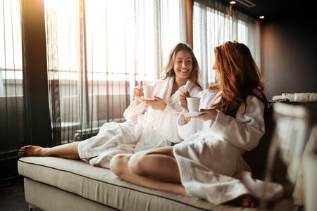 Foto de Women relaxing and drinking tea in robes during wellness weekend - Imagen libre de derechos