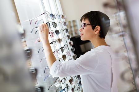 Foto de health care, eyesight and vision concept - happy beautiful woman choosing glasses at optics store - Imagen libre de derechos