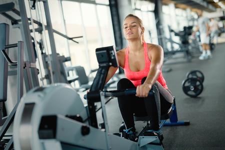 Photo pour Young cute woman doing exercises with rowing machine - image libre de droit