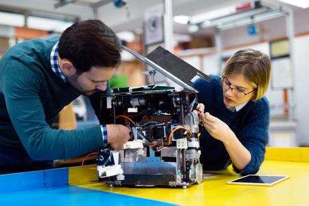 Foto de Young students of robotics preparing robot for testing - Imagen libre de derechos
