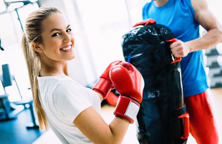 Photo pour Picture of woman wearing boxing gloves in gym - image libre de droit