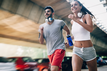 Photo pour Attractive man and beautiful woman jogging together - image libre de droit