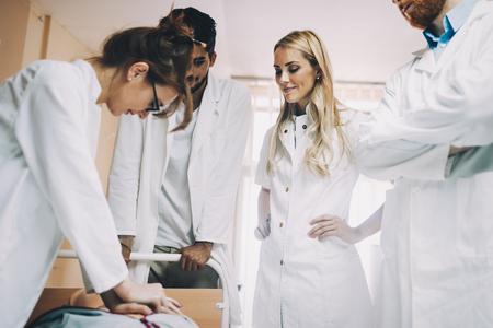 Foto de Group of medical students practicing reanimation task on model - Imagen libre de derechos