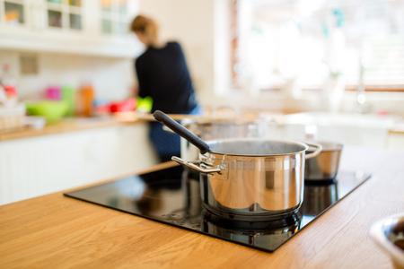Photo pour Housewife making lunch in kitchen - image libre de droit